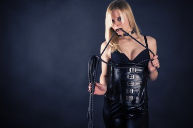Woman in a corset biting whip