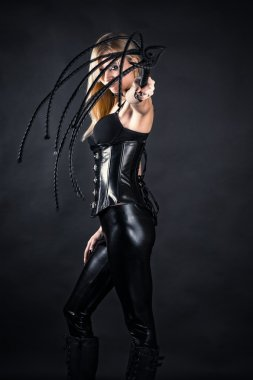 Woman in a corset with a whip in hands