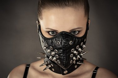 Woman in a mask with spikes isolated on gray