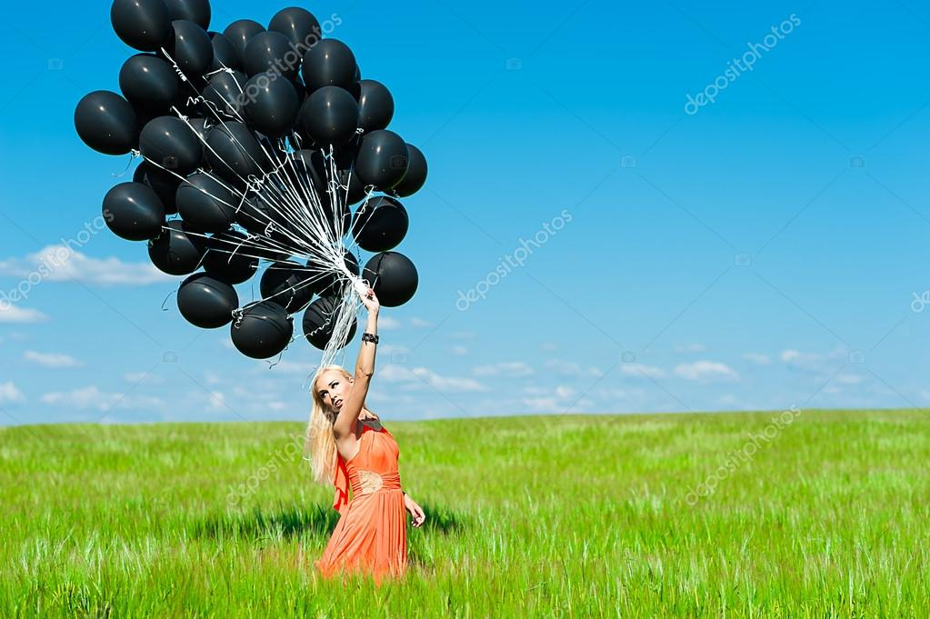 Woman in a dress and black balloons