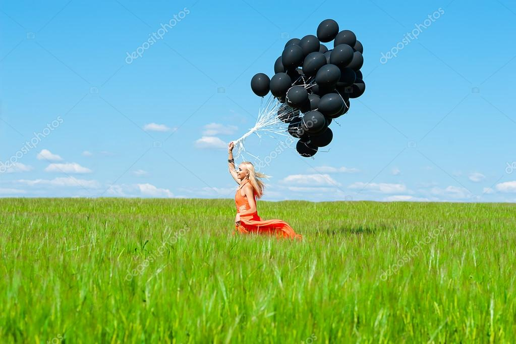 Woman with black balloons running on the green field