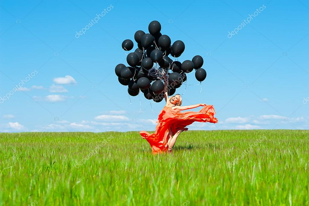 Woman jumping with black balloons in hands