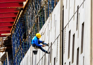 A Construction Workers high up on the wall of a new building.