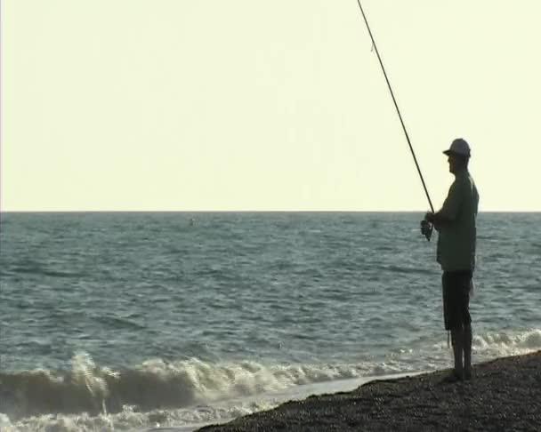 rybář lovící v pobřeží. surfování casting.