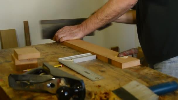 Luthier, carpenter, craftsman, cutting wood with hacksaw