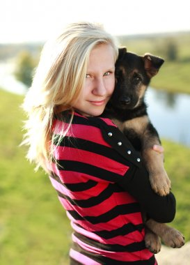 Teen girl holding a German Shepherd puppy in the open air, backlit