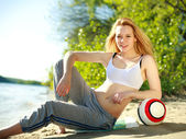 Photo Young sporty woman with ball on the beach, green background