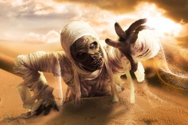 Scary mummy in a desert at sunset