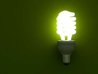 Energy saving compact fluorescent light bulb glowing on green