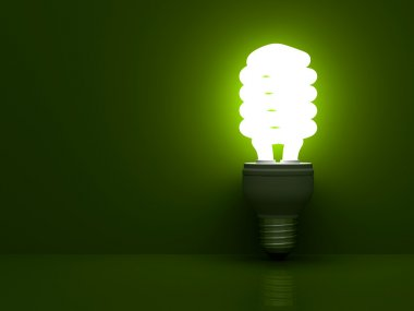 Energy saving compact fluorescent light bulb glowing over green background