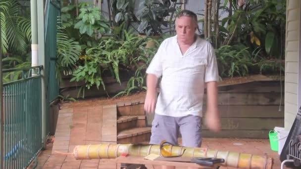viděl dospělé ve věku údržbář procházky do pracovní stůl snížit bambus s rukou