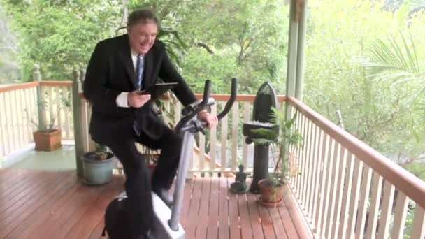 Mature businessman working out on an exercise bike while working with his tablet.