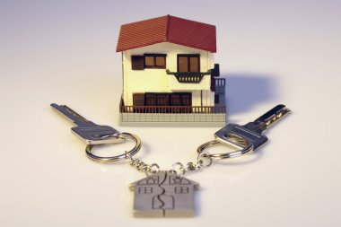 Keys and a small house on a white background