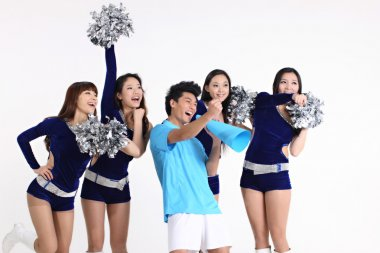 Asian cheerleaders and a man yelling through megaphone