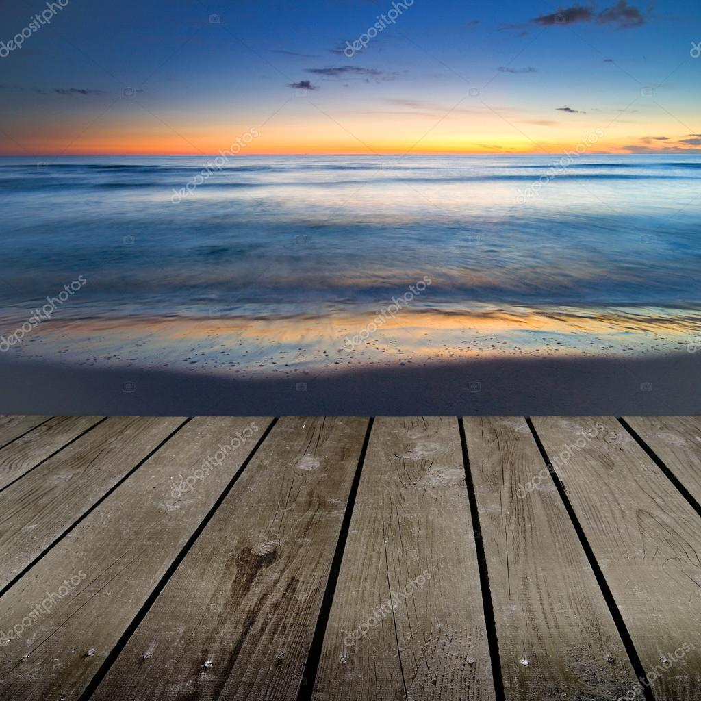 Sunset and empty wooden deck table.