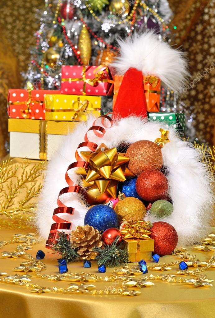 Christmas Hat With Gift Boxes, Baubles On Christmas Tree Backgr U2014 Stock  Photo