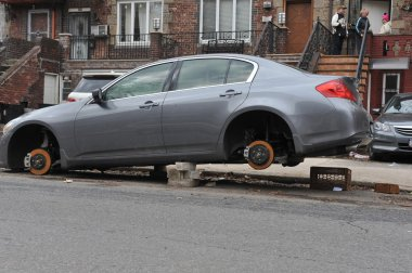 BROOKLYN , NY - NOVEMBER 11: Abandoned flooded car with stolen wheels left on bricks in the residential area after impact from Hurricane Sandy in Brooklyn, New York, U.S., on November 11, 2012.