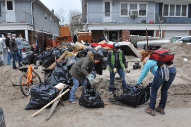 QUEENS, NY - NOVEMBER 11: Volunteers cleaning debris and sand in the Rockaway beach residential area from Hurricane Sandy in Queens, New York, U.S., on November 11, 2012.