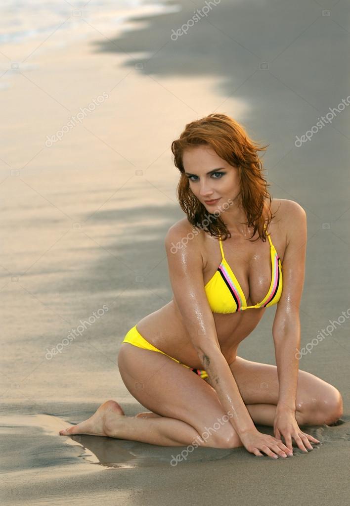 Fashion model in custom design yellow bikini sitting pretty on the sunset beach