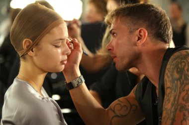 NEW YORK- SEPTEMBER 11: Make-up artist applying makeup to model backstage at the Blonds Collection for Spring/ Summer 2013