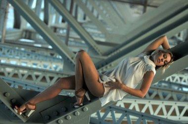 Girl wears bikini standing under the bridge