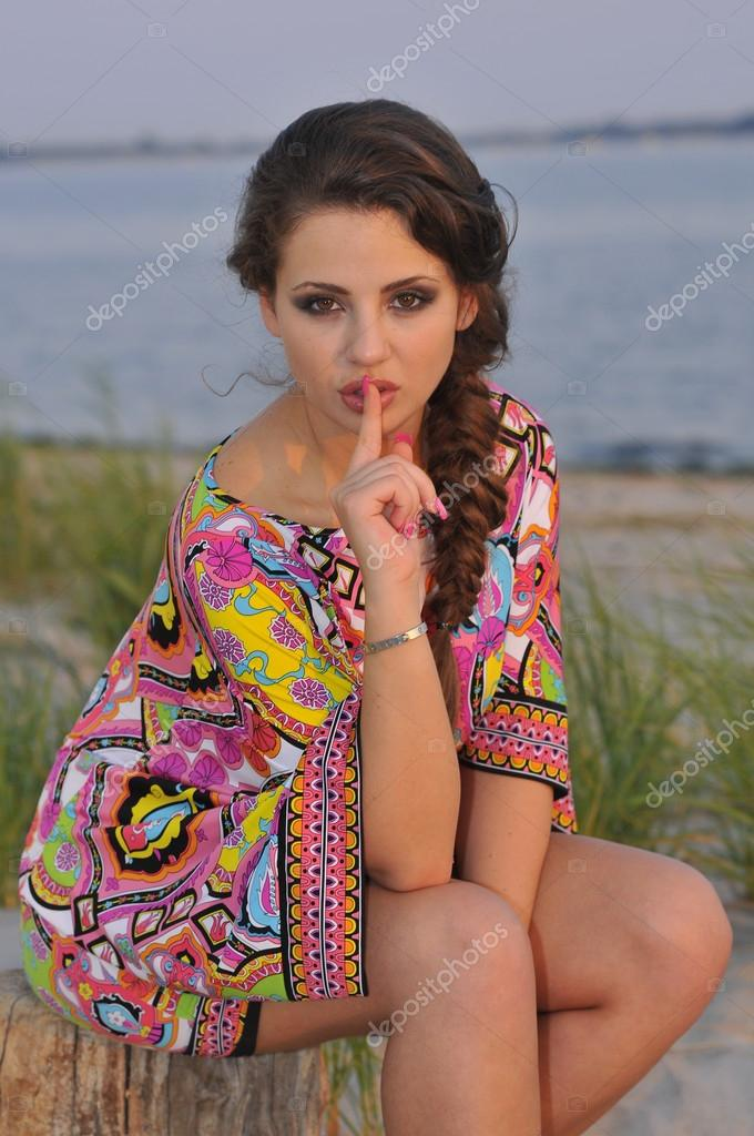 Beautiful brunette model posing pretty at tropical beach wearing short designers colorful dress