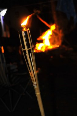 Camp fire and flame of a bamboo torch burning in the night.