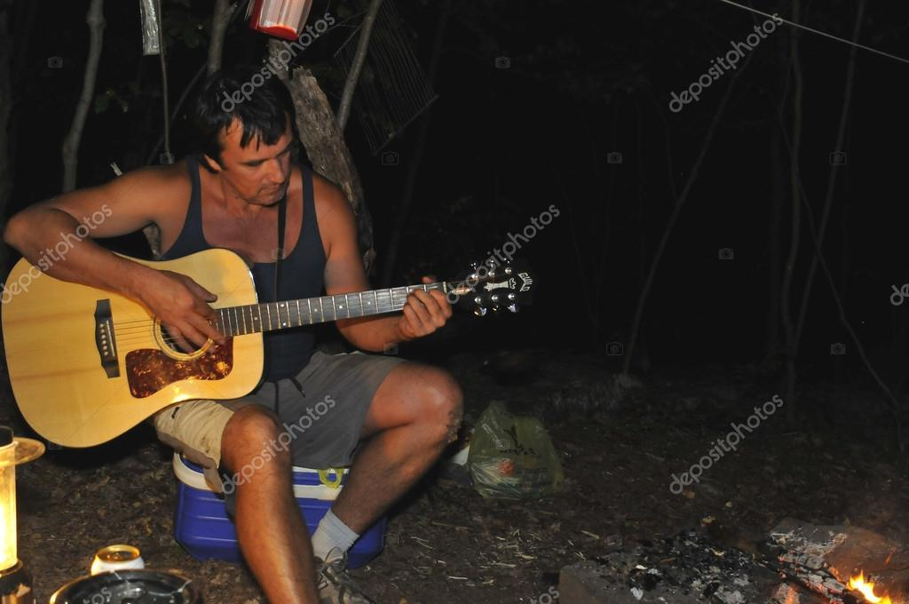 Playing guitar at night campground