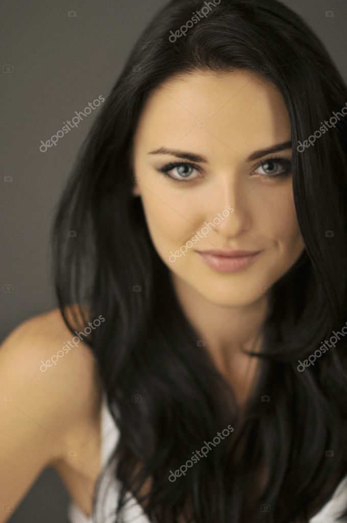 Attractive smiling young brunette woman with blue eyes. Shallow depth of field, focus on eyes.