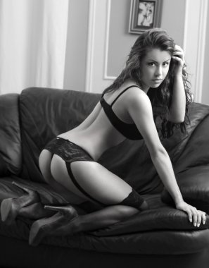 A young brunette woman posing sexy in lingerie at black leather sofa love seat