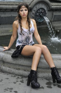 Fashion model sitting in front of fountain in New York City park