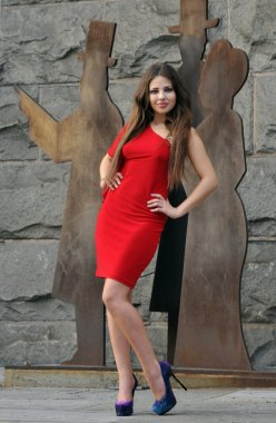 Fashion model posing in short red dress in front of wall in New York City park