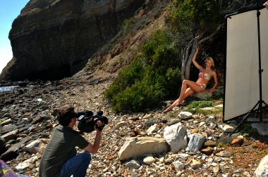 Photo video crew on location set with bikini model