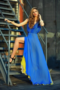 Fashion model posing sexy, wearing long blue evening dress on rooftop location