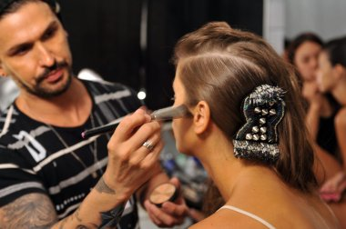 Model during hair and makeup process and first looks backstage at the Agua Bendita Collection