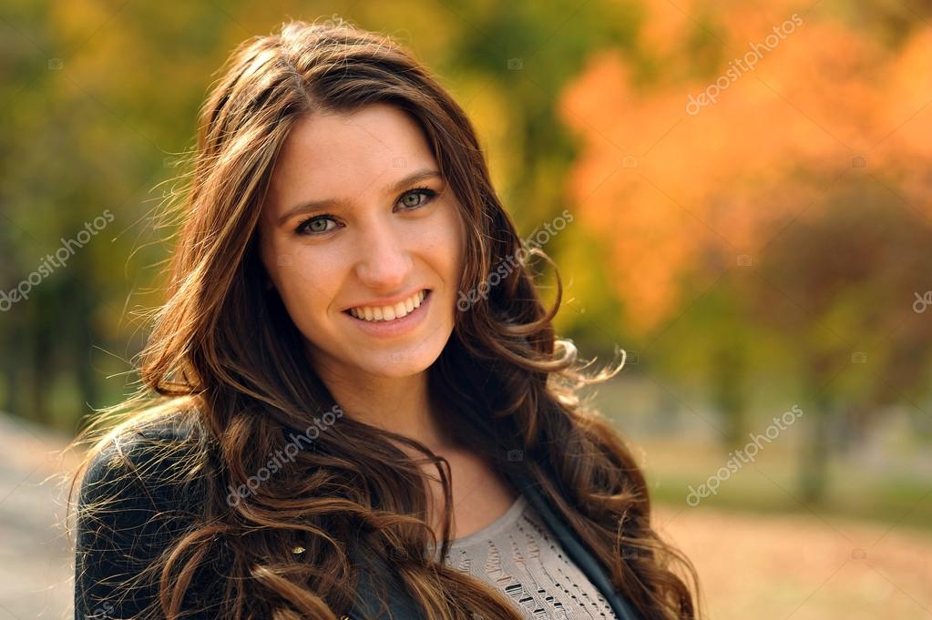 Beautiful elegant woman sitting on the bench in a autumnal park