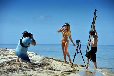 Photographer shooting model on the beach