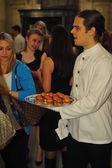 Waiters serve before Ralph Lauren show
