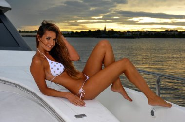 Seductive model posing on sailboat in sunset