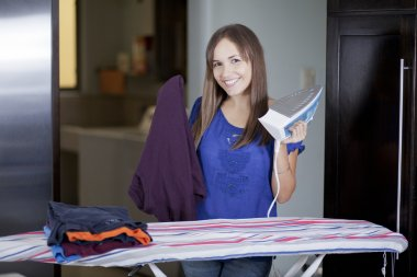Happy young woman ironing on ironing board at home, smiling.