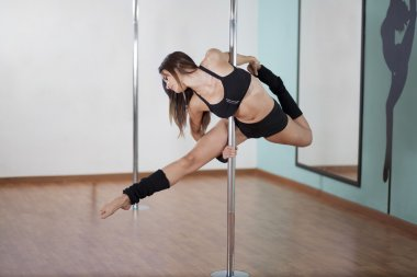 Young beauty woman exercise pole dance