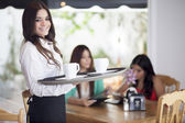 Fotografie Portrait of young waitress holding a tray