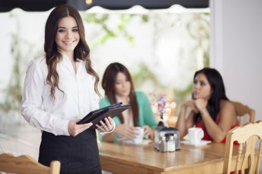 Portrait of a young waitress and customers