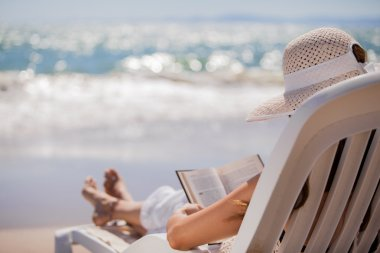 Beautiful woman reading a book on beach