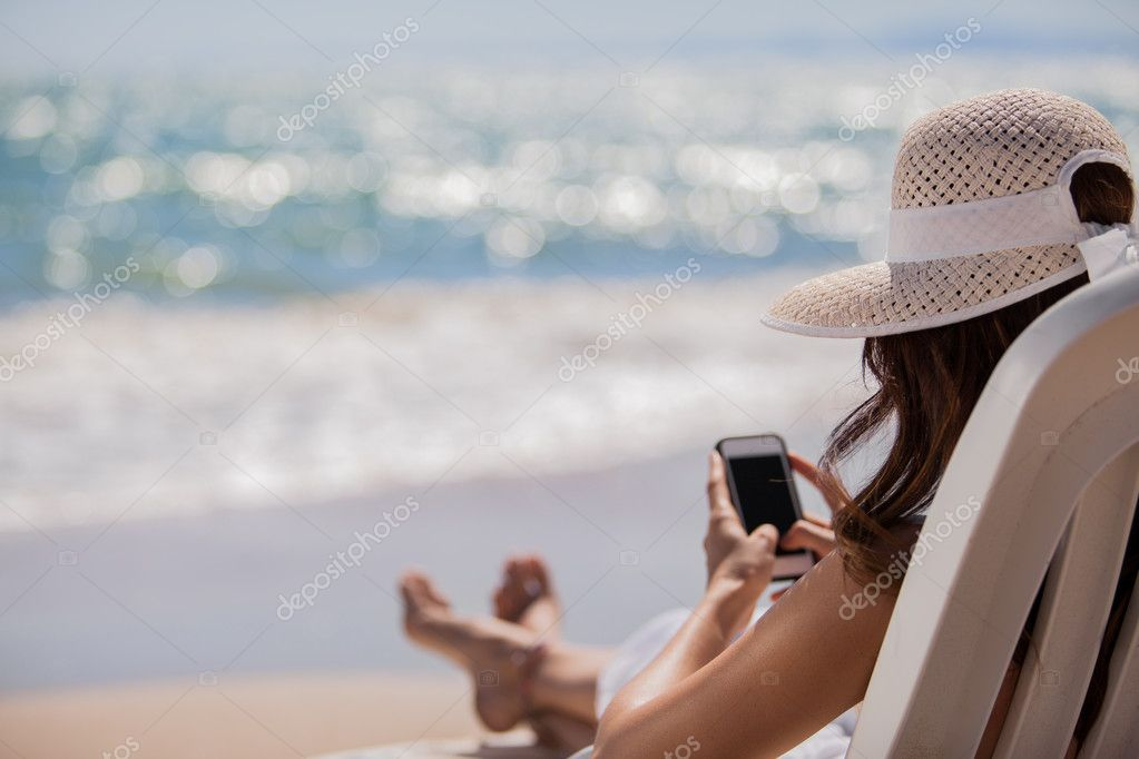 Young woman with mobile phone on a beach