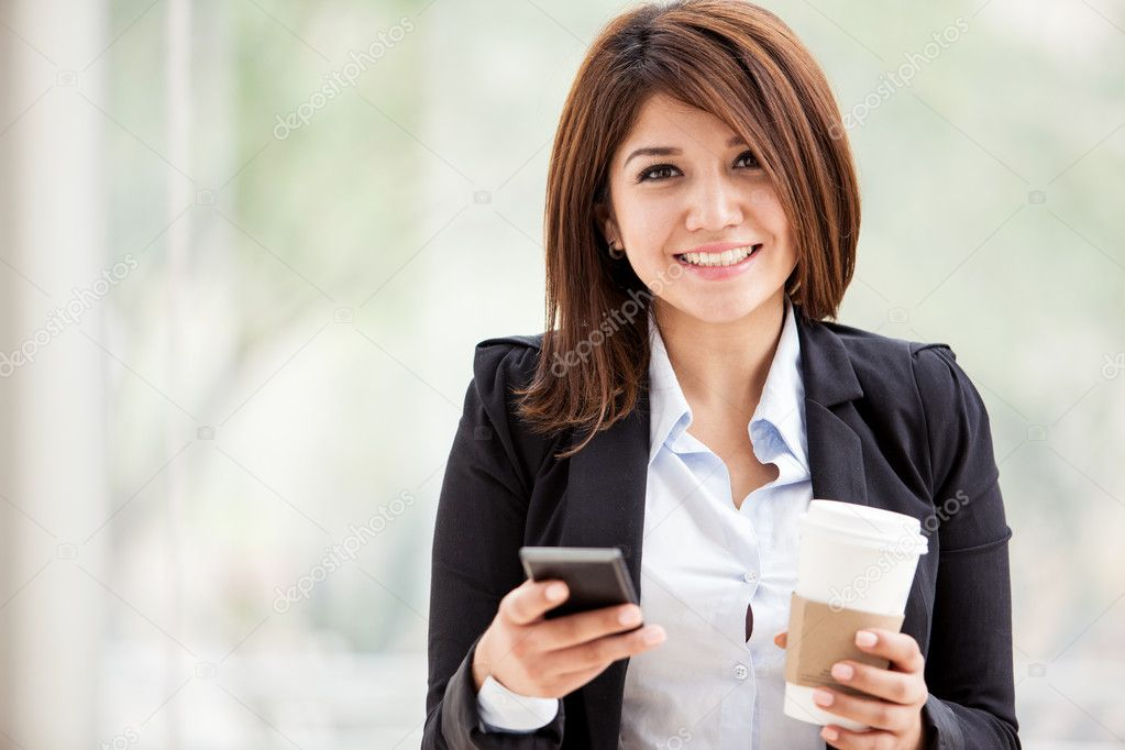 beautiful smile business woman texting on her cell phone and holding a cup of coffee
