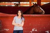 Frau steht neben ihrem Pferd im Stall