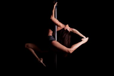 Woman holding a difficult pose in a pole fitness class