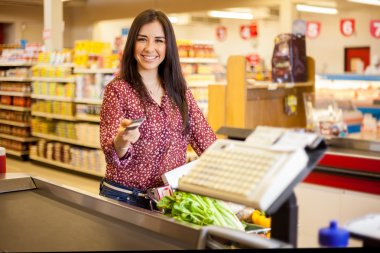 Cute  young woman standing with a trolley with products in the store at checkout and paying with credit card