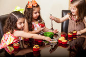 Sweet little girls decorating some cupcakes together at home